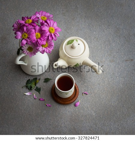 Cup of tea and purple flowers on gray background, selective focus top view, still life style - stock photo