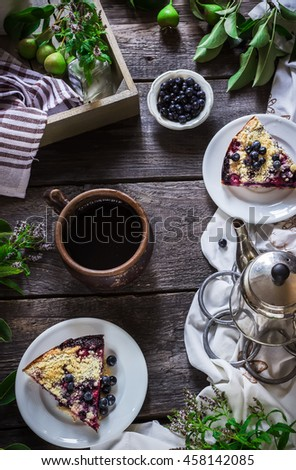 Cup of tea and slice of blueberry pie on dark wooden background. Style rustic. Selective focus. - stock photo