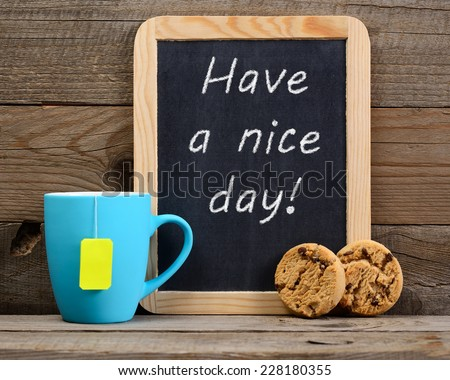 Cup of tea and small blackboard with Have a nice day! phrase - stock photo