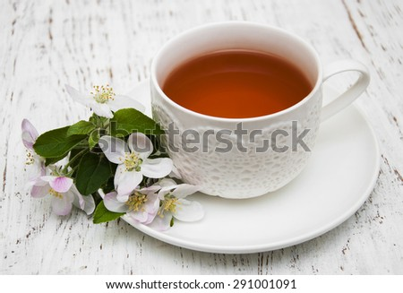 Cup of tea and spring apple blossom on a wooden background
