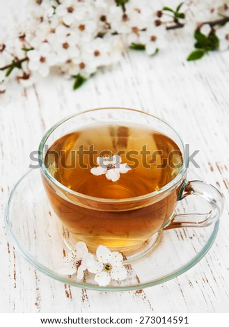 Cup of tea and spring apricot blossom on a wooden background