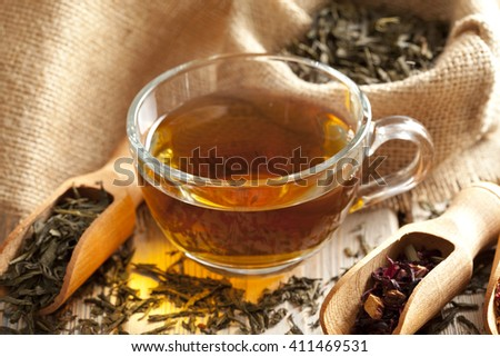 Cup of tea and tea leaves on wooden table - stock photo