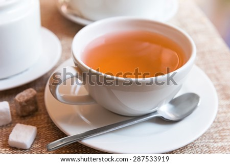 Cup of tea and tea pot on table - stock photo