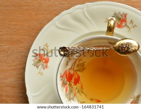 Cup of tea and teaspoon on wooden - stock photo