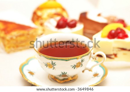 Cup of tea and various cakes -shallow DOF - stock photo