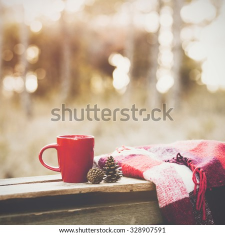 Cup of tea and warm plaid blanket on wooden rustic bench in the autumn forest. Fall weekend. Photo toned, selective focus. - stock photo