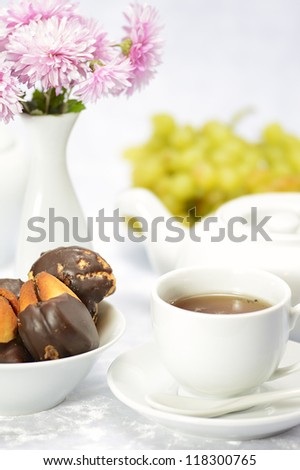 cup of tea, cake and grapes on a white background in high key