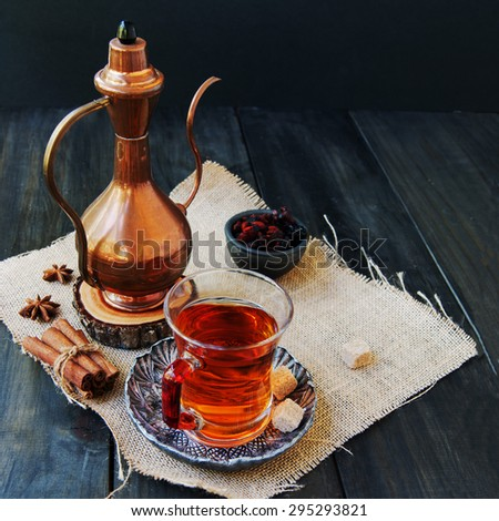 cup of tea, cinnamon, anise, teapot and flowers on wooden background