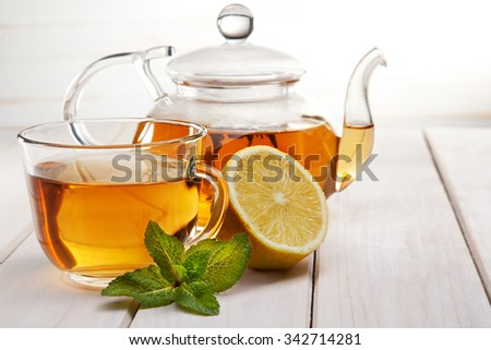 cup of tea, glass teapot, mint and lemon on a wooden table - stock photo