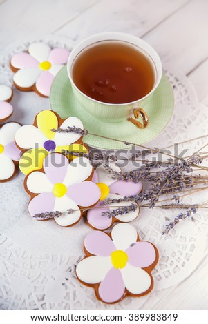 Cup of tea, handmade cookies like flowers on white wooden table. - stock photo