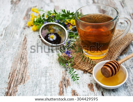 Cup of tea, honey and flowers on a old wooden background - stock photo