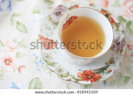 Cup of tea in floral cup on flower print cloth - stock photo