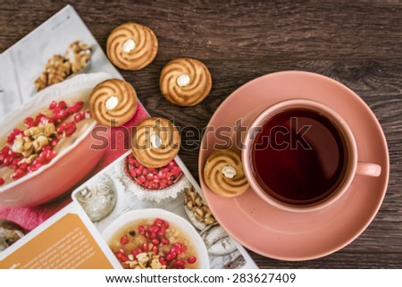 Cup of tea in pink mug and biscuits with magazine - stock photo