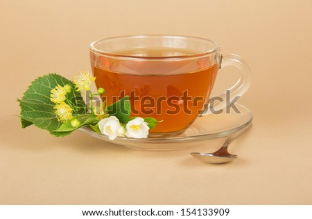 Cup of tea, linden and jasmine flowers, on a beige background