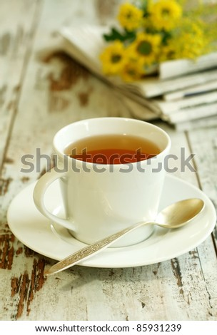 cup of tea, newspaper and flowers on old wooden boards - stock photo
