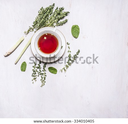 cup of tea on a saucer with a set of herbal tea thyme, mint, lemon grass on wooden rustic background top view with text area, vintage style - stock photo