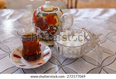 Cup of tea on the saucer, teapot and sugar bowl - stock photo