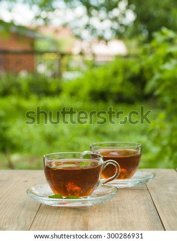 Cup of tea on the wooden table in the garden - stock photo