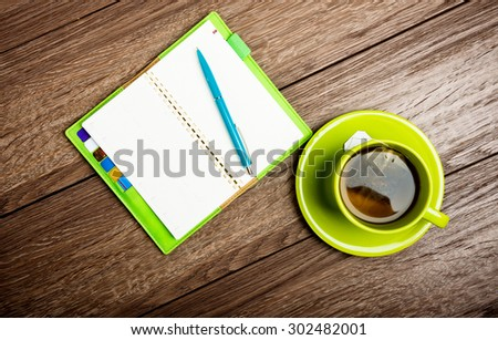 cup of tea, pen, opened organizer on the wooden table - stock photo