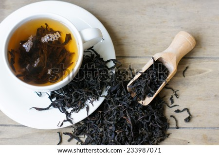 Cup of tea surrouded dry tea leaveas - stock photo