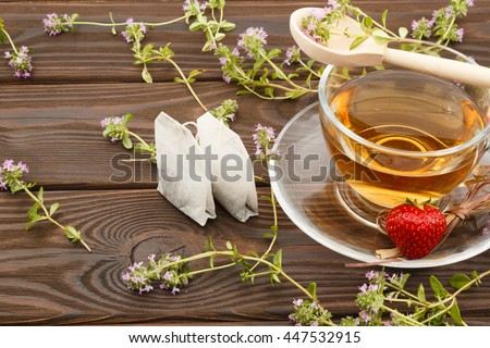 cup of tea, tea bags, thyme, strawberries and a wooden spoon on a wooden background