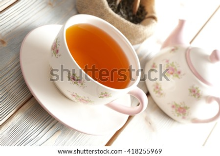 Cup of tea, teapot and dried tea leaves on wooden table  - stock photo