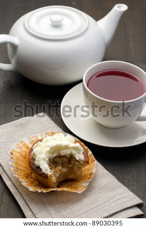 Cup of tea, teapot and muffin - stock photo