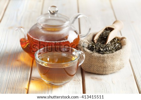 Cup of tea, teapot and tea leaves on wooden table