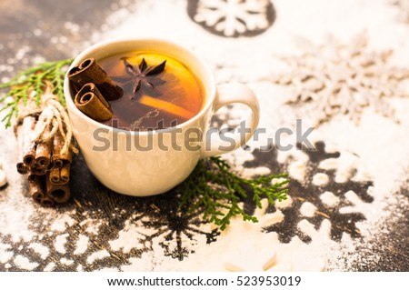 Cup of Tea with a Lemon and Cinnamon on Christmas background with snow in rustic style with copyspace