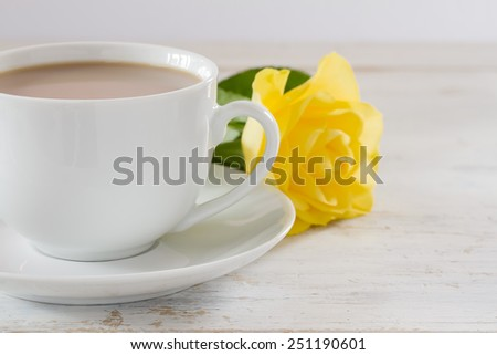 Cup of tea with a single yellow rose - stock photo