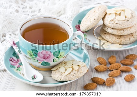 Cup of tea with almond cookies and almonds slices  - stock photo