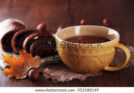 Cup of tea with autumn decor on wooden table.  - stock photo