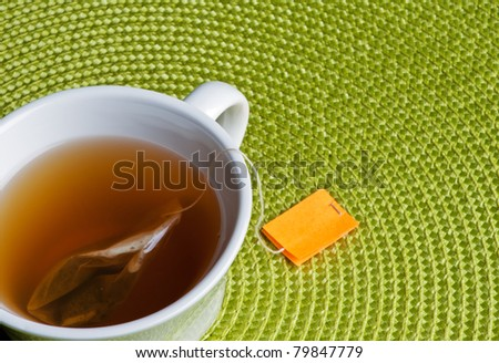 Cup of tea with bag and green place mat. - stock photo