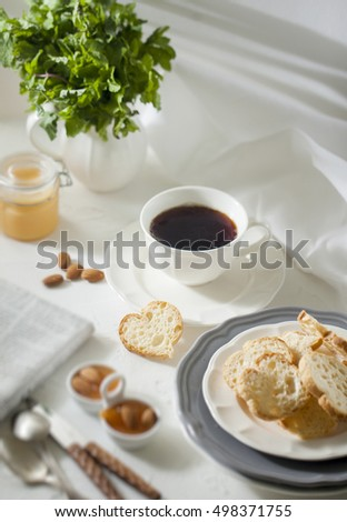 Cup of tea with biscuits and apricot jam on the white table with morning newpaper