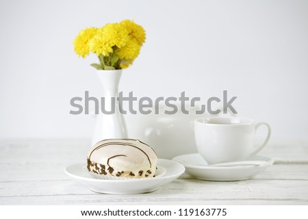 Cup of tea with bread rings on white table - stock photo