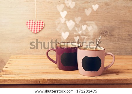 Cup of tea with chalkboard stickers  and heart bokeh on wooden table - stock photo