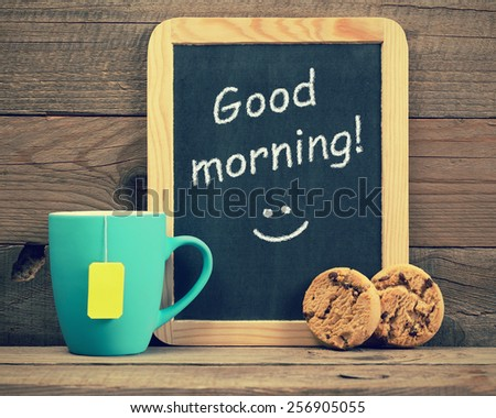 Cup of tea with cookies and blackboard with phrase Good morning! - stock photo
