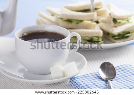 Cup of tea with cucumber sandwiches in background - stock photo