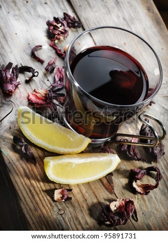 Cup of tea with dried hibiscus and lemon slices - stock photo