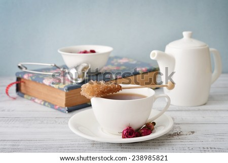 Cup of tea with dry rose buds and tea strainer in the shape of heart