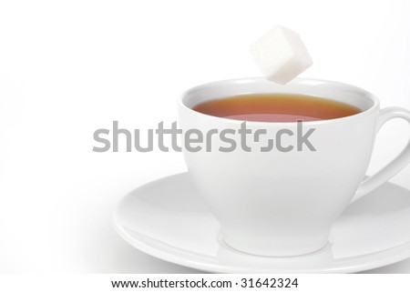 Cup of tea with falling sugar cube - stock photo