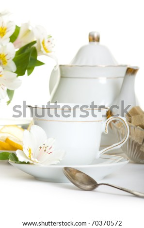 Cup of tea with flower.Teaset on table isolated over white - stock photo