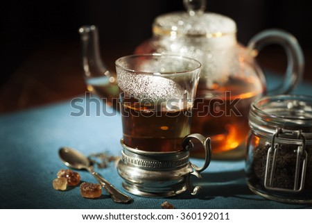 Cup of tea with glass tea pot on the background