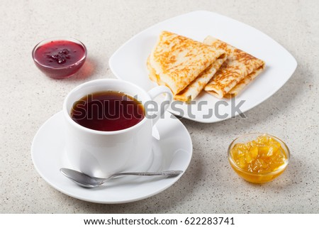 Cup of tea with jam, sour cream and russian pancakes - blini.