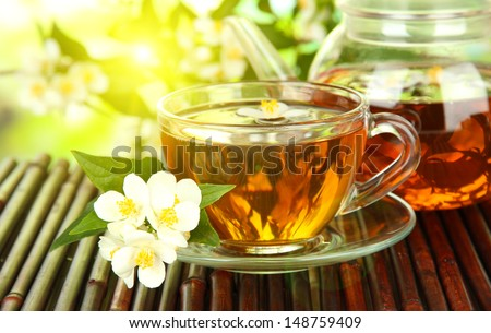 Cup of tea with jasmine, on bamboo mat, close-up - stock photo