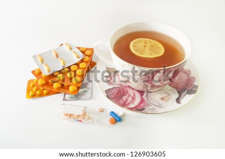 Cup of tea with lemon and a lot of medicines isolated on white - curing cold symptoms - stock photo