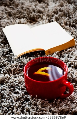 Cup of tea with lemon and book on gray background. Selective focus. - stock photo