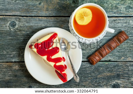Cup of tea with lemon and cheesecake on a wooden background - stock photo