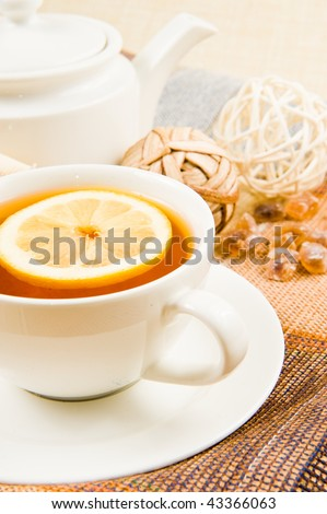 cup of tea with lemon and the pot on tissue background