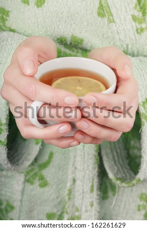 Cup of tea with lemon in woman hands - stock photo